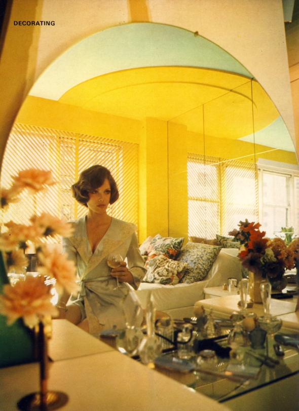 Lois Chiles relaxes with a glass of white wine, looking every inch the rising star. Bed strewn with cushions acts as extra seating, huge mirror tiles make the room look twice as large. Glass dressing table shelf laden with old scent bottles, lovingly collected over the years.