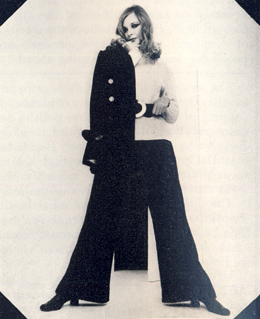 Black velvet trouser suit by Carrot on Wheels. Beige polo necked sweater by McCaul. Black belt with perspex buckle by Dior. Leather shoes by Charles Jourdan.