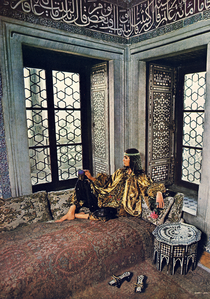 In the Baghdad Room of Topkapi, full of the ghosts of harem women, black and gold decorations to wear, baggy drawstring trousers, silks, velvets, netted and worked with gilded peacocks for a rich top with immense sleeves gathered in twice. By Bill Gibb for Baccarat. High lifted sandals at Thea Porter.