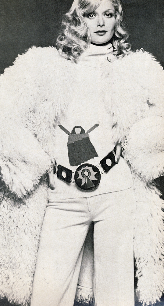 Mongolian lamb coat designed by Moya Bowler for Antartex.  Angora and lambswool sweater with figure knitted into the front and wide cream wool jersey trousers both by Sonia Rykiel. Wooden painted belt by Bugs Young.