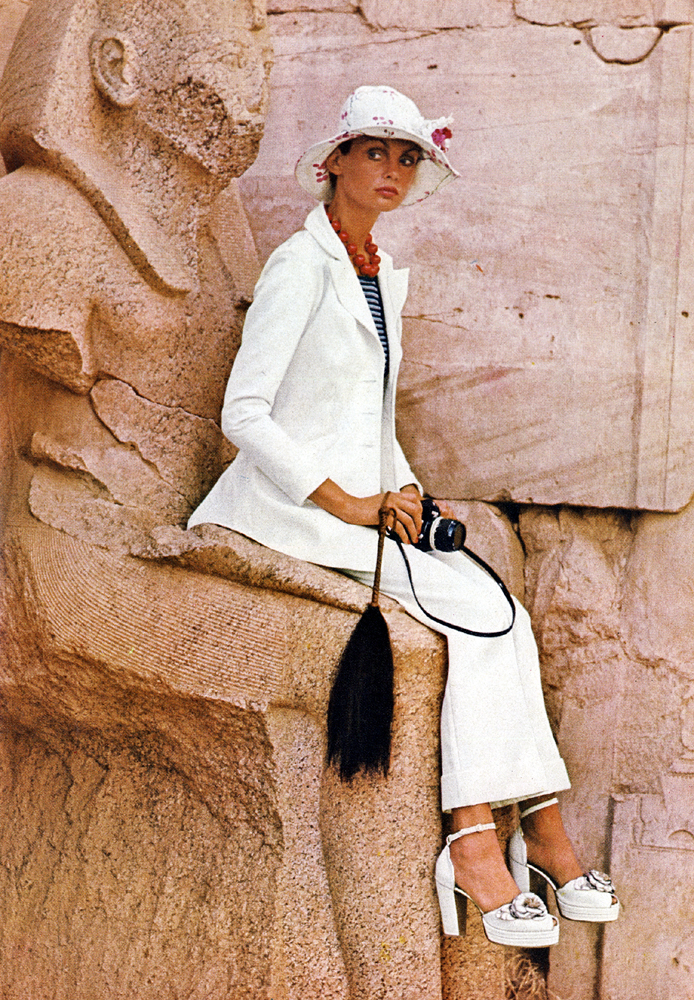 At the temple of Karnak, Jean Shrimpton wears a white Terylene gabardine suit in sharp and beautiful shape. Ossie Clark at Quorum. White hite at Feathers. White platforms shoes with silver roses, by Richard Smith for The Chelsea Cobbler.