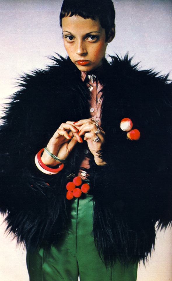 Chunky fake fox Borg jacket with orange satin lining and shiny satin trousers both from Wallis Shops. Feather embossed crepe de chine shirt by Ronnie Stirling at Stirling Cooper. Dog brooch by Corocraft. Rings by Adrien Mann. Flocked peaches and cherries both by Adrien Mann.