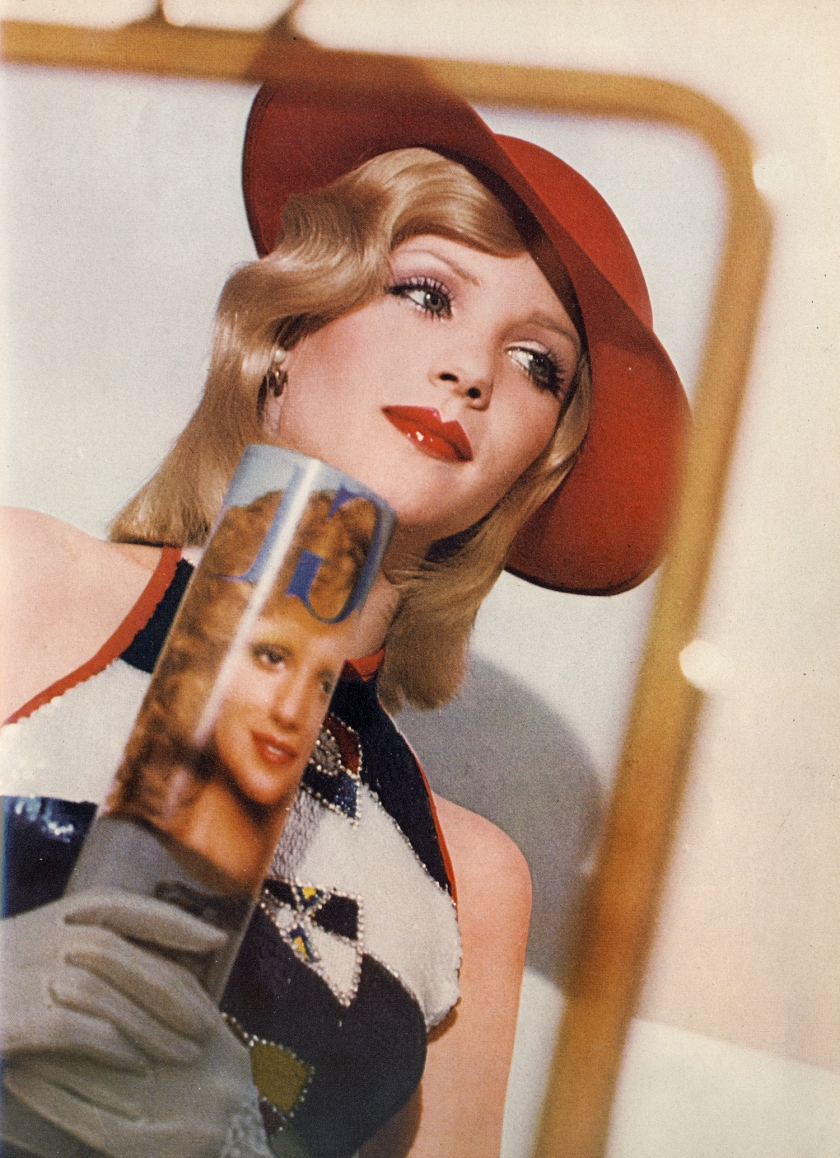The shallow red straw hat by Herbert Johnson. Sequined halter top of flags flying and stripes by Walter Albini. White loves by Kir. Hair by Jean Louis David, Paris.